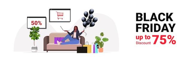 Afrikaanse amerikaanse vrouw die goederen op laptop online winkelen zwarte vrijdag grote verkoop vakantie kortingen concept woonkamer interieur kopie ruimte