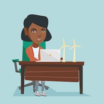 Afrikaanse arbeider die van windmolenpark aan laptop werkt.