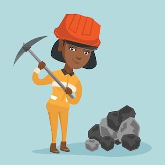 Afrikaanse mijnwerker in bouwvakker die met een pikhouweel werkt.