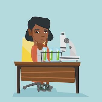 Afrikaanse student die in laboratoriumklasse werkt.