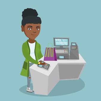 Afrikaanse vrouw die draadloos met een slim horloge betaalt.