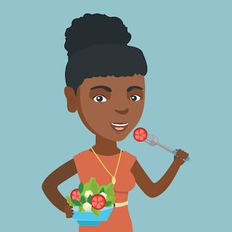 Afrikaanse vrouw die gezonde plantaardige salade eet.