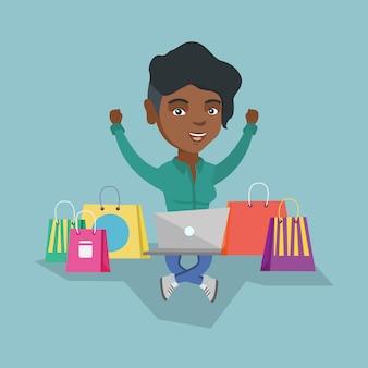 Afrikaanse vrouw die laptop voor online het winkelen gebruikt
