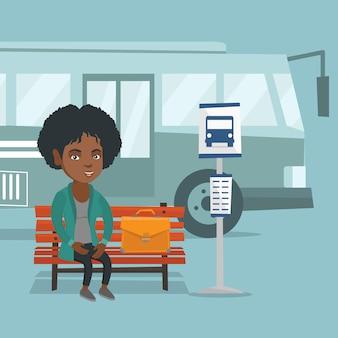 Afrikaanse vrouw die op een bus bij de bushalte wacht.