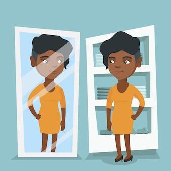 Afrikaanse vrouw die op kleding in kleedkamer probeert.