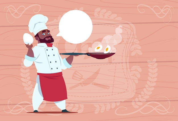 Afro-amerikaanse chef-kok holding koekenpan met eieren lachende cartoon chief in white restaurant uniform over houten getextureerde achtergrond