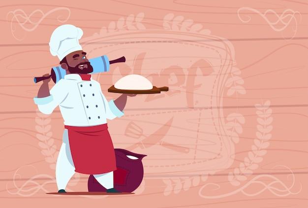 Afro-amerikaanse chefkok houden bloem en deeg glimlachend cartoon chef in wit restaurant uniform over houten gestructureerde achtergrond