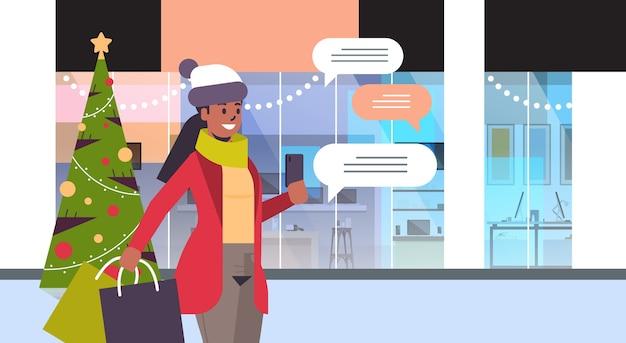 Afro-amerikaanse meisje met boodschappentassen met behulp van chatten mobiele app op smartphone sociaal netwerk chat zeepbel communicatie kerstvakantie concept portret horizontale vectorillustratie