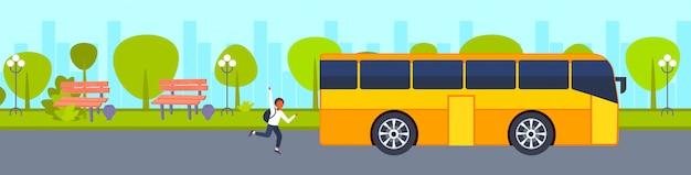 Afro-amerikaanse tiener loopt om schoolbus te halen, schiet op laat concept mannelijke student zwaaien handgebaar stad stedelijk park landschap achtergrond horizontaal