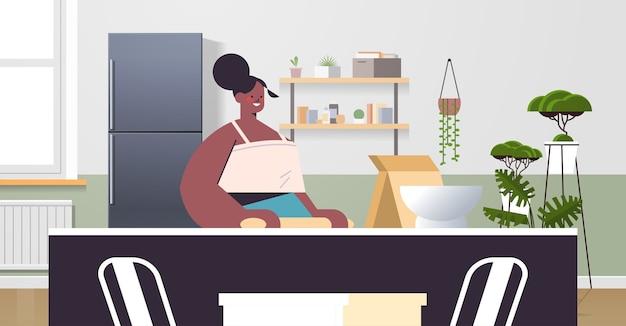 Afro-amerikaanse vrouw bereiden van voedsel thuis koken concept moderne keuken interieur horizontaal portret