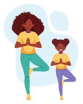 Afro-amerikaanse vrouw die yoga doet met dochter