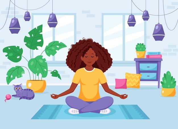 Afro-amerikaanse vrouw mediteert in lotushouding in een gezellig modern interieur
