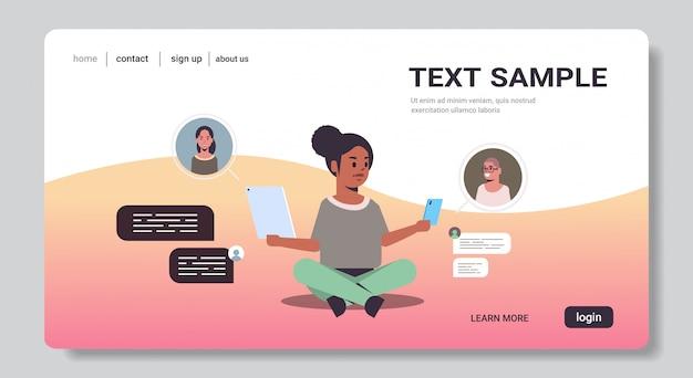 Afro-amerikaanse vrouw met behulp van chatten apps op digitale apparaten sociaal netwerk chat bubble communicatieconcept