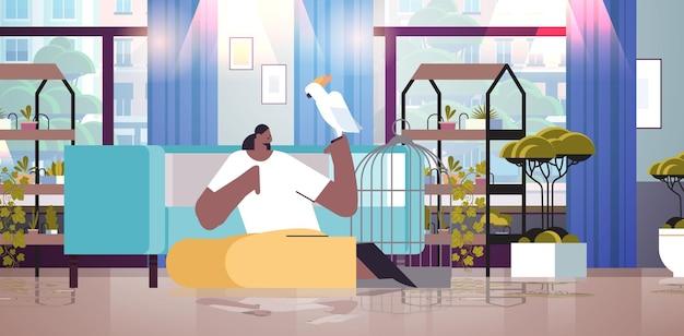 Afro-amerikaanse vrouw met papegaaienmeisje die zorgt voor huisdier, vogel, woonkamer, interieur horizontaal