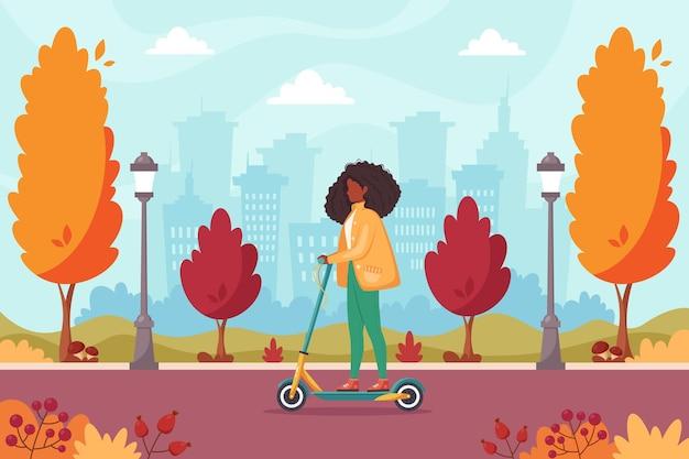 Afro-amerikaanse vrouw rijdt op elektrische scooter in herfstpark