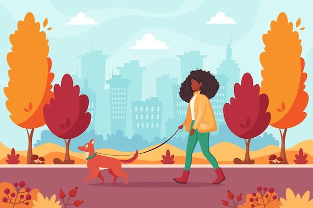 Afro-amerikaanse vrouw wandelen met hond in herfst park autumn