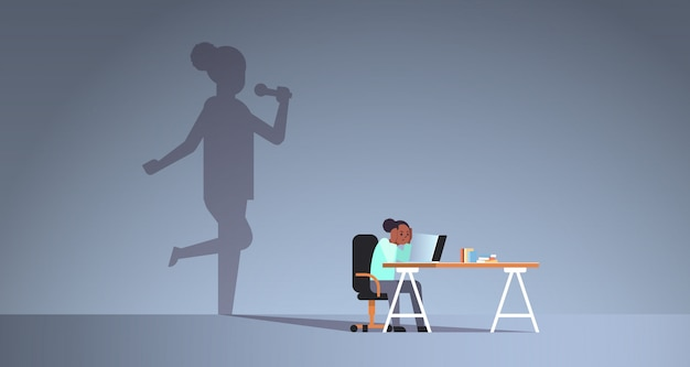 Afro-amerikaanse vrouw zittend op de werkplek met behulp van laptop