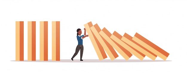 Afro-amerikaanse zakenvrouw stoppen domino-effect crisismanagement kettingreactie financieren interventie conflictpreventie concept horizontale volledige lengte