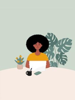 Afro vrouw die op laptop werkt