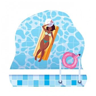 Afrovrouw met vlottermatras die in water drijven