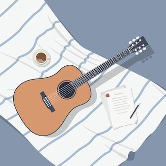 Akoestische gitaar met muzieknoten op een wit-blauwe deken