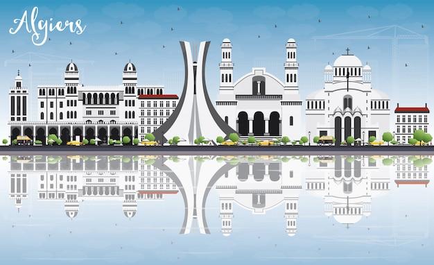 Algiers skyline met grijze gebouwen, blauwe lucht en reflecties.