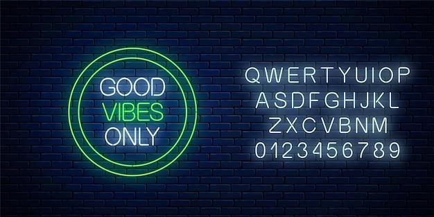 Alleen goede vibes, gloeiende neon inscriptie zin in groene cirkelframe met alfabet op donkere bakstenen muur