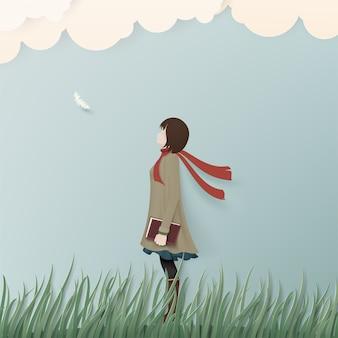 Alleen meisje in winterjas op groen gras met boek.