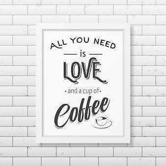 Alles wat je nodig hebt is liefde en een kopje koffie - citeer typografisch realistisch vierkant wit frame op de bakstenen muur.