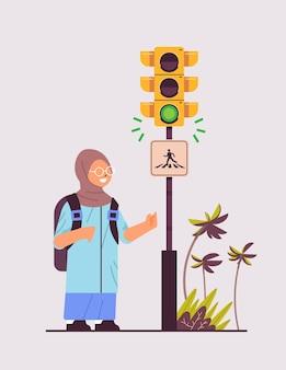 Arabisch schoolmeisje dat met rugzak op groen verkeerslicht wacht om de weg over te steken op het verkeersveiligheidsconcept van de zebrapad
