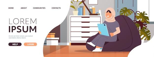 Arabisch schoolmeisje met behulp van tablet pc arabisch meisje zittend op een zitzak en huiswerk onderwijs concept woonkamer interieur horizontale volledige lengte kopie ruimte vectorillustratie