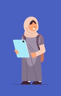Arabisch schoolmeisje met behulp van tablet pc glimlachend meisje met gadget verticale volledige lengte vectorillustratie