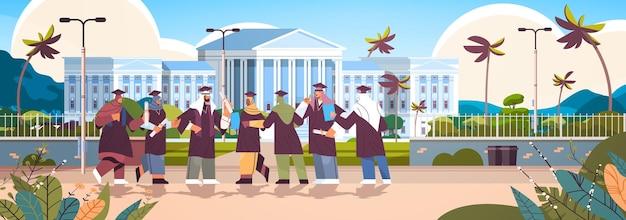 Arabische afgestudeerde studenten staan samen in de buurt van universiteitsgebouwen die arabische afgestudeerden vieren en academisch diploma behalen