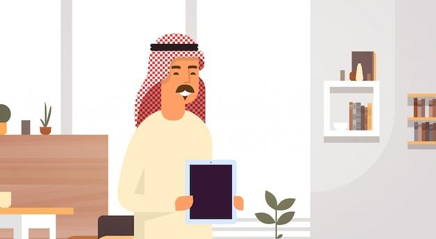 Arabische bedrijfsmens die de lege ondernemer van de tabletcomputer in modern bureau houden