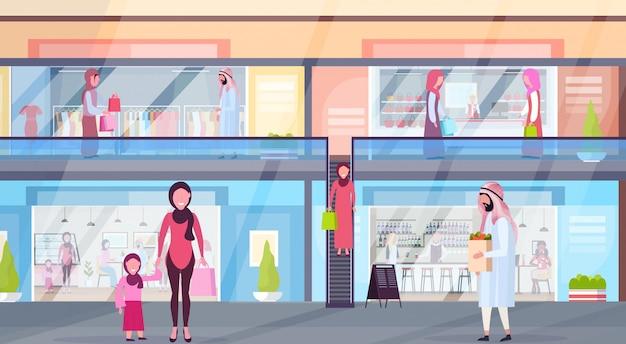 Arabische bezoekers lopen modern winkelcentrum met kleding boetieks en coffeeshops supermarkt detailhandel interieur arabische mensen in traditionele kleding horizontale volledige lengte plat