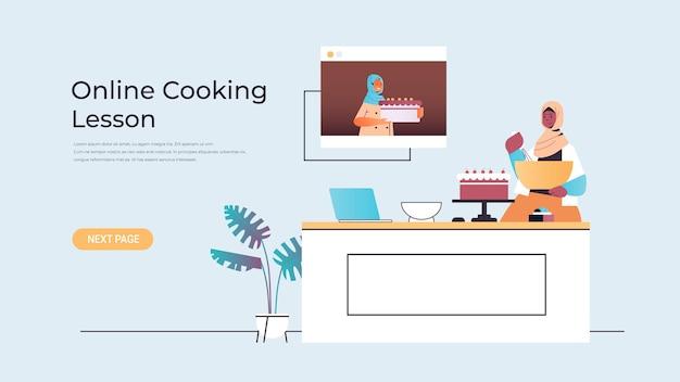 Arabische blogger van het vrouwenvoedsel die cake voorbereidt tijdens het bekijken van videozelfstudie met arabische chef-kok in webbrowservenster
