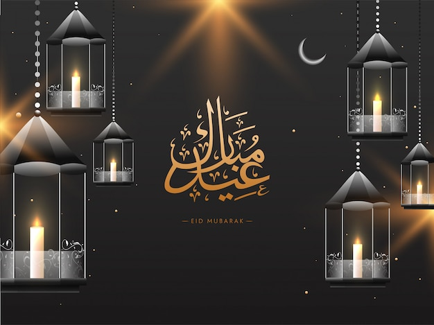 Arabische islamitische kalligrafische tekst eid mubarak, en hangende verlichte lantersn op grijze achtergrond. nacht zicht. islamitische festival viering concept.
