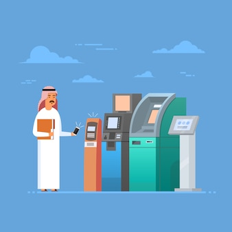 Arabische man met atm machine cell slimme telefoon mobiele betaling, islam zakenman dragen traditionele cl