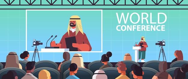 Arabische mannelijke arts die toespraak houdt op tribune met microfoon medische conferentie vergadering geneeskunde gezondheidszorg concept collegezaal interieur horizontale afbeelding