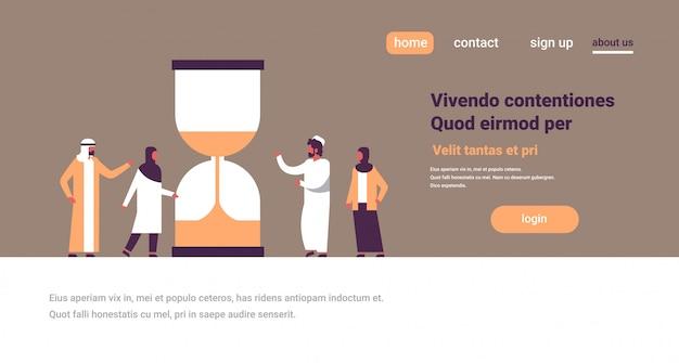 Arabische mensen groeperen staande zandloper tijd deadline banner