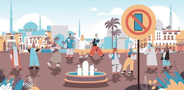 Arabische mensen lopen stadspark geen gsm-zone digitaal detox-concept smartphone in verbodsbord verlaten internet sociale netwerken stadsgezicht achtergrond horizontale afbeelding