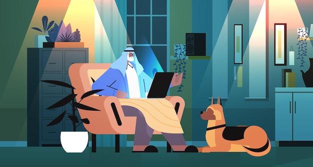 Arabische senior man met laptop arabische grootvader met hond aan het werk in donkere nacht woonkamer