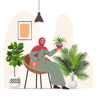Arabische vrouw die van kamerplantenwoonkamer of huistuinbinnenland zorgt