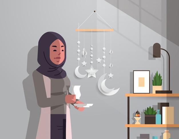 Arabische vrouw in traditionele kleding drinken koffie vieren ramadan kareem heilige maand moderne woonkamer interieur plat verticaal portret