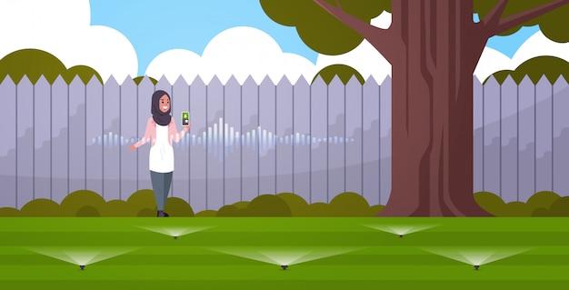 Arabische vrouw met behulp van mobiele app controle irrigatie gras watergeefsysteem