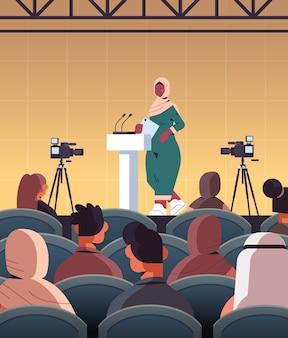 Arabische vrouwelijke arts die toespraak geeft op tribune met microfoon medische conferentie vergadering geneeskunde gezondheidszorg concept collegezaal interieur verticale afbeelding