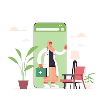 Arabische vrouwelijke arts met ehbo-kit in smartphonescherm chat bubble communicatie online overleg gezondheidszorg geneeskunde medisch advies concept