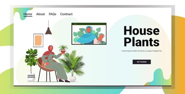 Arabische vrouwen die voor kamerplanten zorgen meisjes met virtuele bijeenkomst tijdens videogesprek woonkamer interieur horizontale kopie ruimte