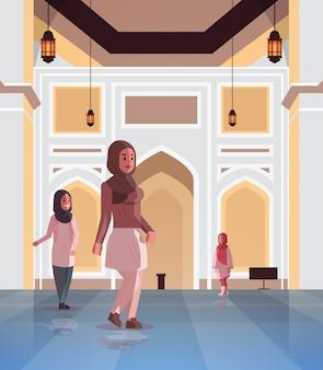 Arabische vrouwen komen naar nabawi moskee bouwen moslim religie concept arabische mensen in traditionele kleding ramadan kareem heilige maand plat volledige lengte verticaal