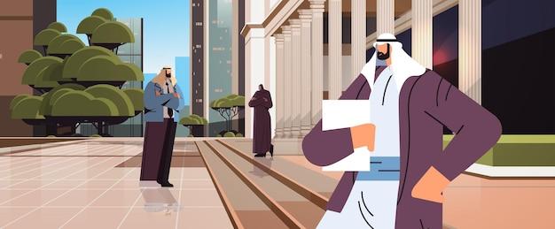 Arabische zakenliedenadvocaten die zich dichtbij overheidsgebouw met kolommenwet en rechtvaardigheids juridisch adviesconcept bevinden